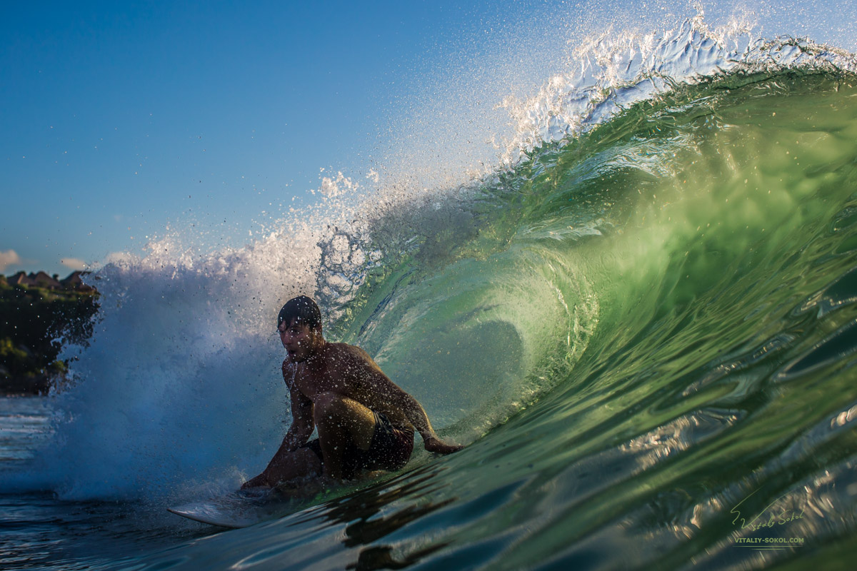 Surfing in Bali.Surfer inside a Tube Wave lit with beautiful Sunset Light
