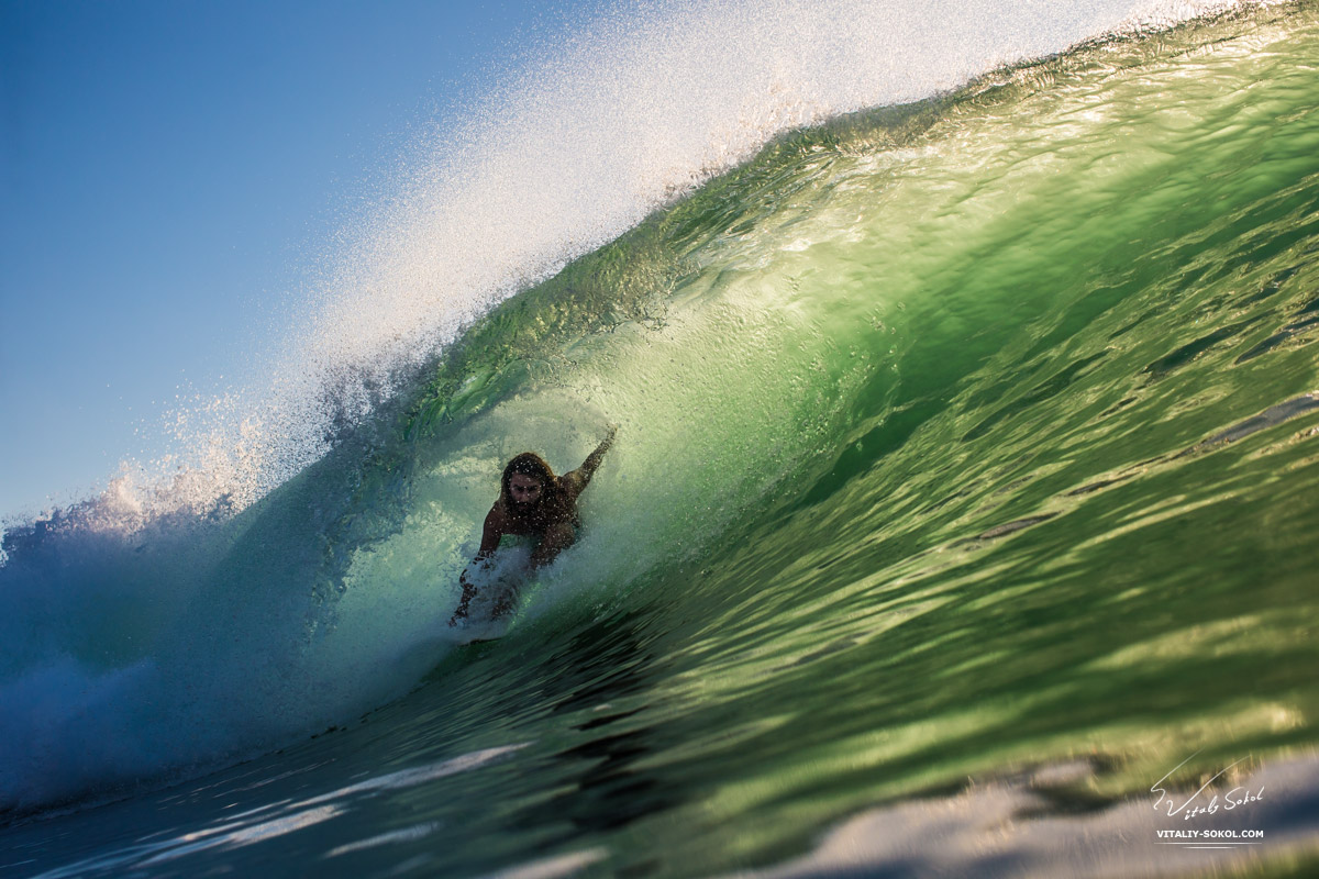 Surfing in Bali. Surfer riding inside a Tube Wave lit with beautiful Sunset Light