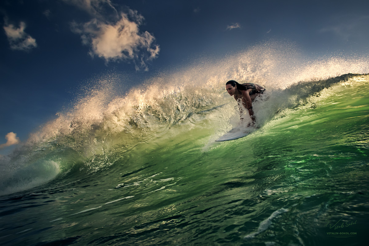 A surfer girl starting from shining ocean snuset green bright wave