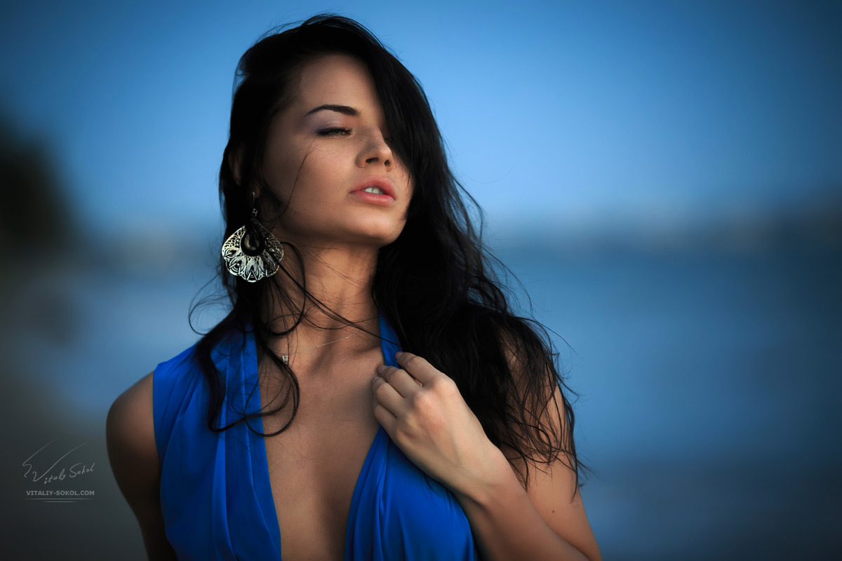 Portrait of a beautiful brunette woman near sea at evening. Dark hair and blue dress