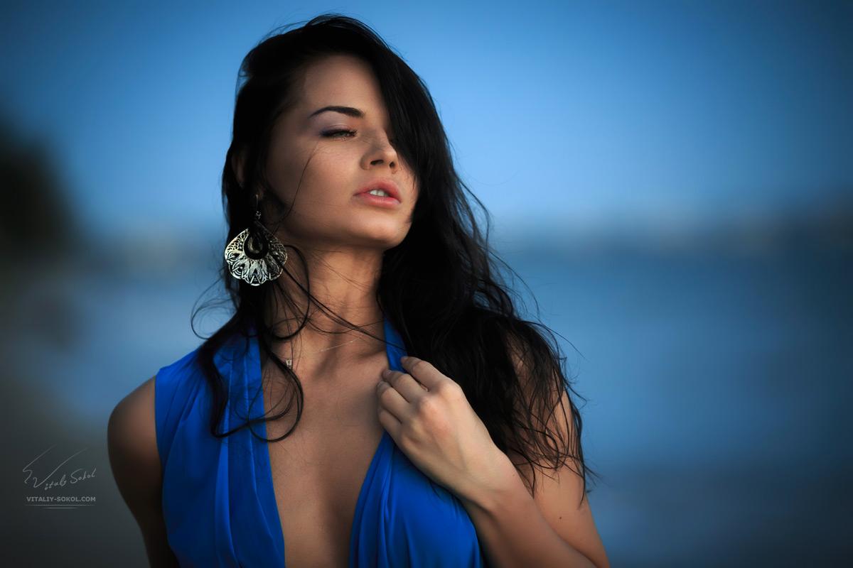 Portrait of a beautiful brunette woman near sea at evening. Dark hair and blue dress