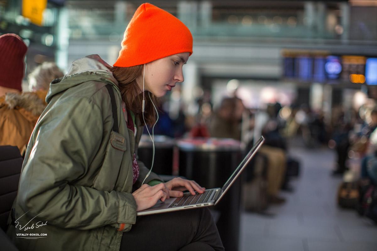 Девушка с ноутбуком в зале ожидания аэропорта