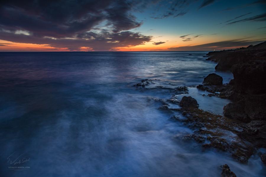 Скалистый берег в океане и закатное небо