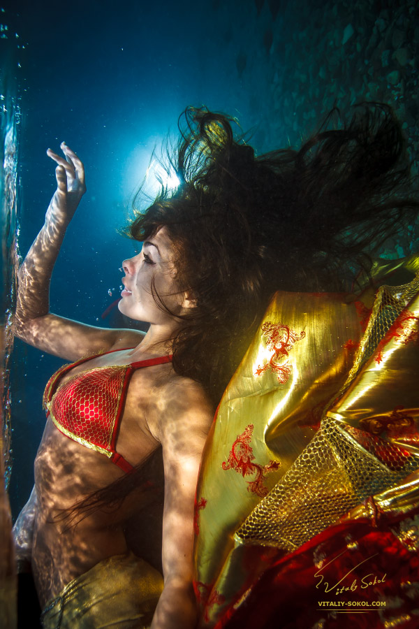 Brunette wearing red dress underwater shot