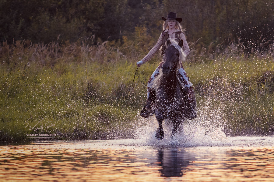 Cowboy girl riding horse through water