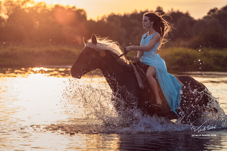 Girl riding horse through water
