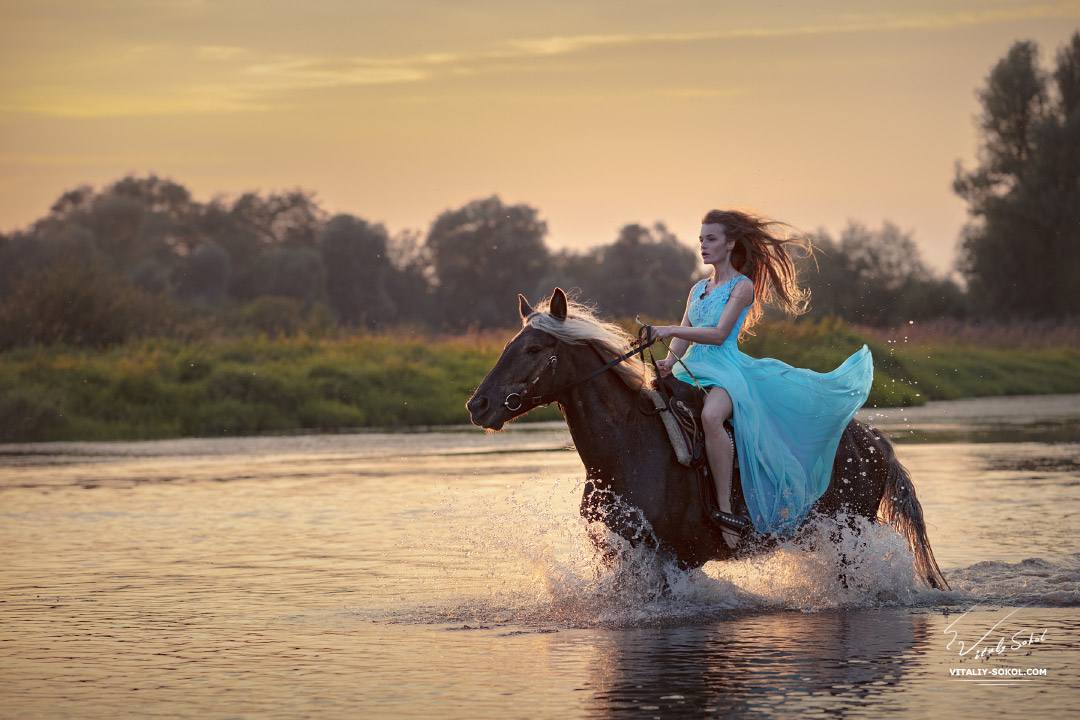Девушка в платье скачет по воде на лошади