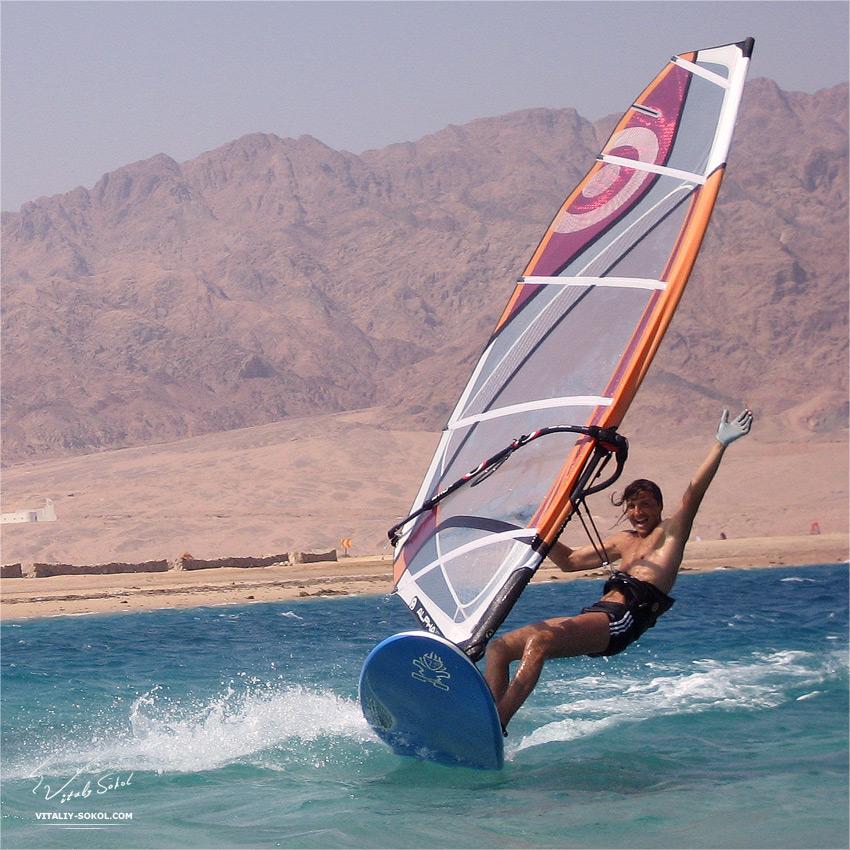 Виталий Сокол на доске для серфинга с улыбкой на счастливой роже рассекает волны Лагуны