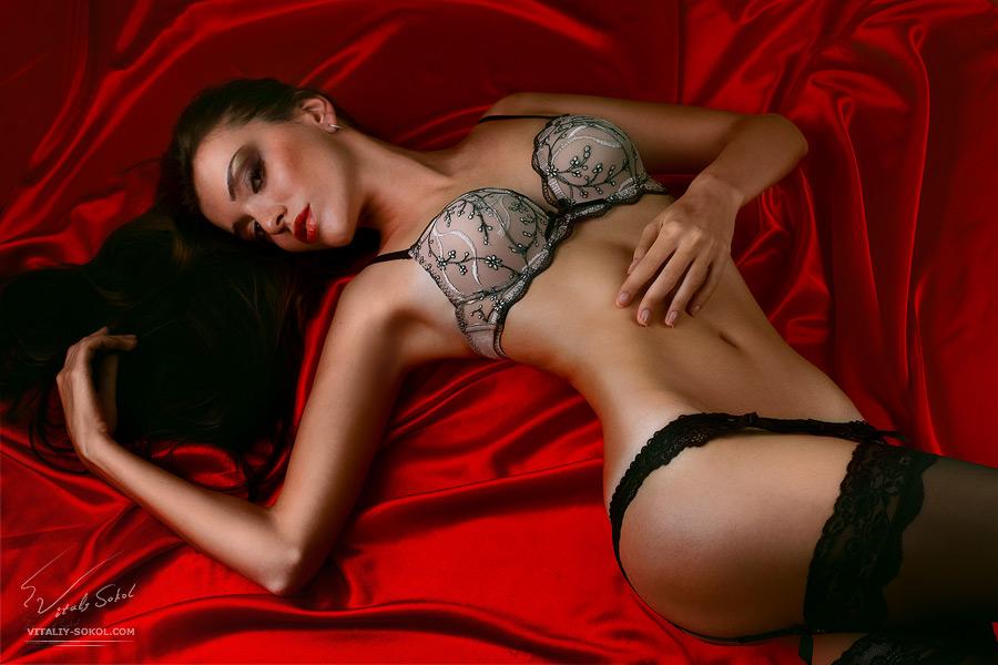 Красивая стройная модель в сексуальном белье лежит на красном атласе