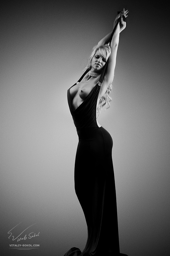 Красивая женщина в черном обтягивающем вечернем платье медленно обнажается.