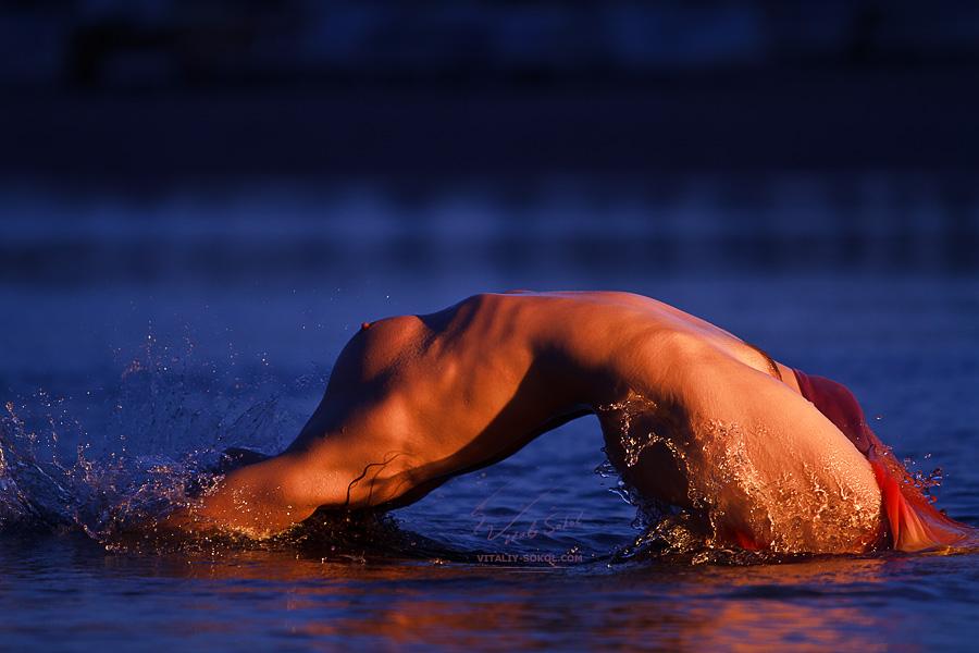 Обнажённая красивая девушка выпрыгивает из воды