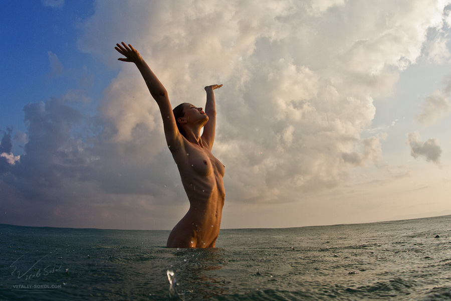 Beautiful naked model in the sea under colorful sky