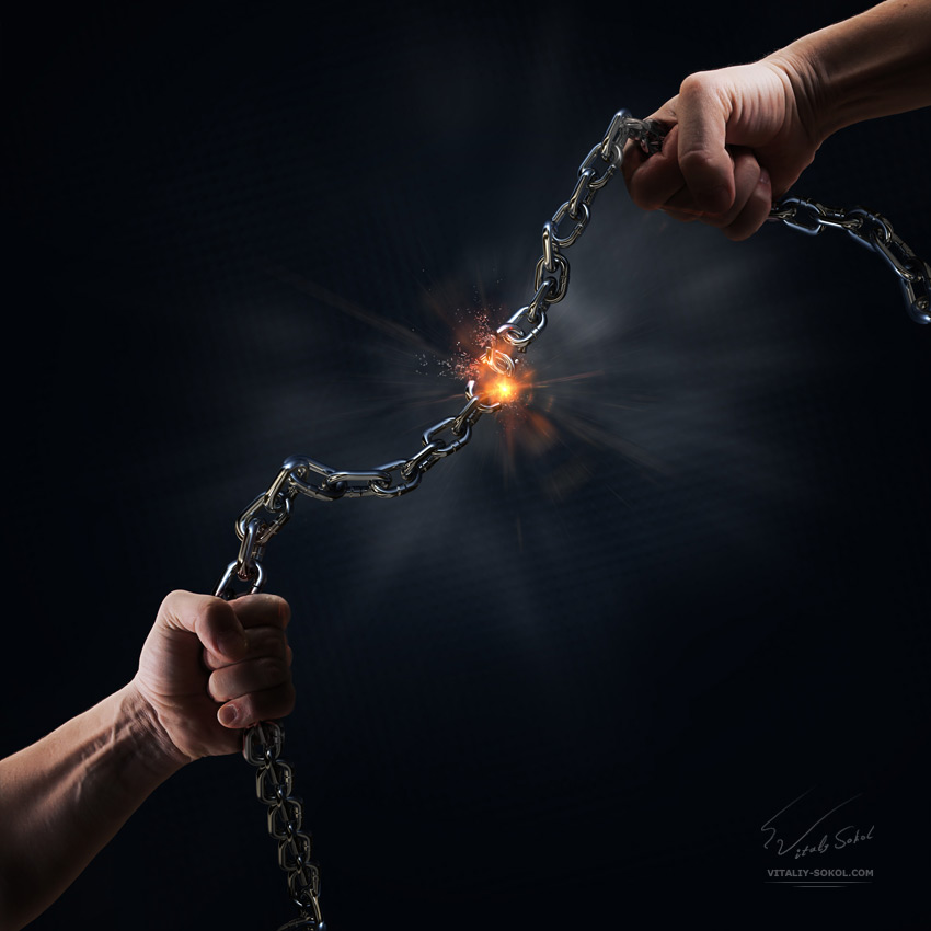 man tearing a heavy steel chain by hands as a conceptual symbol of freedom