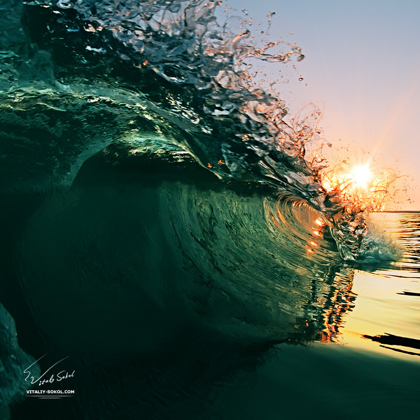 beautiful breaking glossy ocean wave crashing near the beach at sunset time