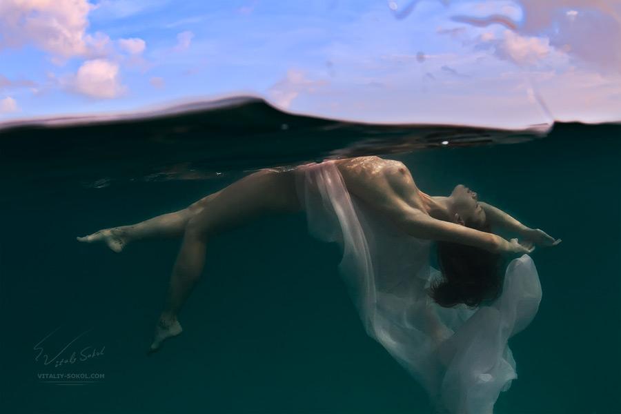 Подводная фотография обнажённой девушки в разрезе водной среды с облаками над уровнем воды. Фото Виталия Сокола,  Underwater Nude, sea background