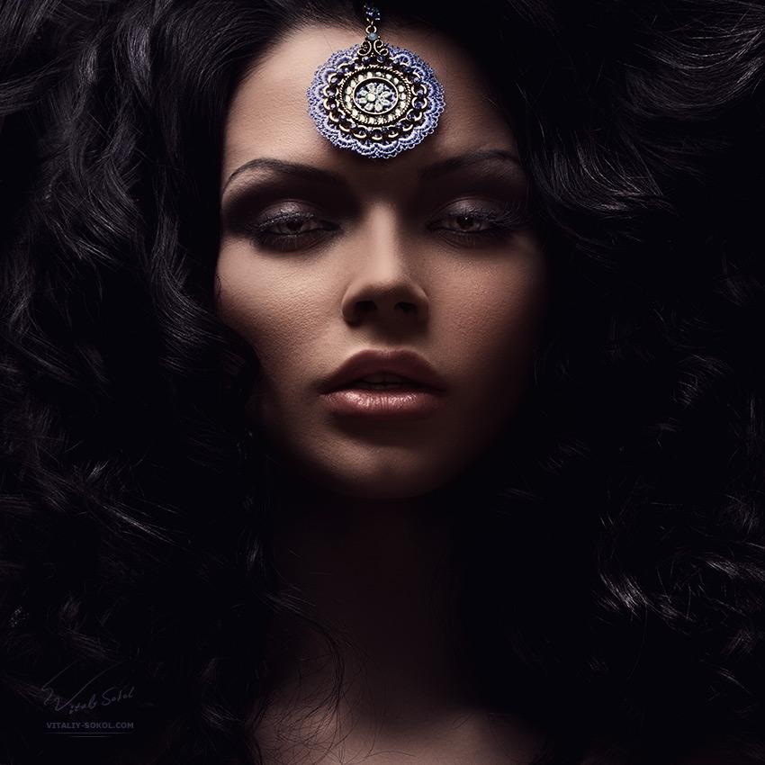 Low key portrait. Beautiful female face with dark hair