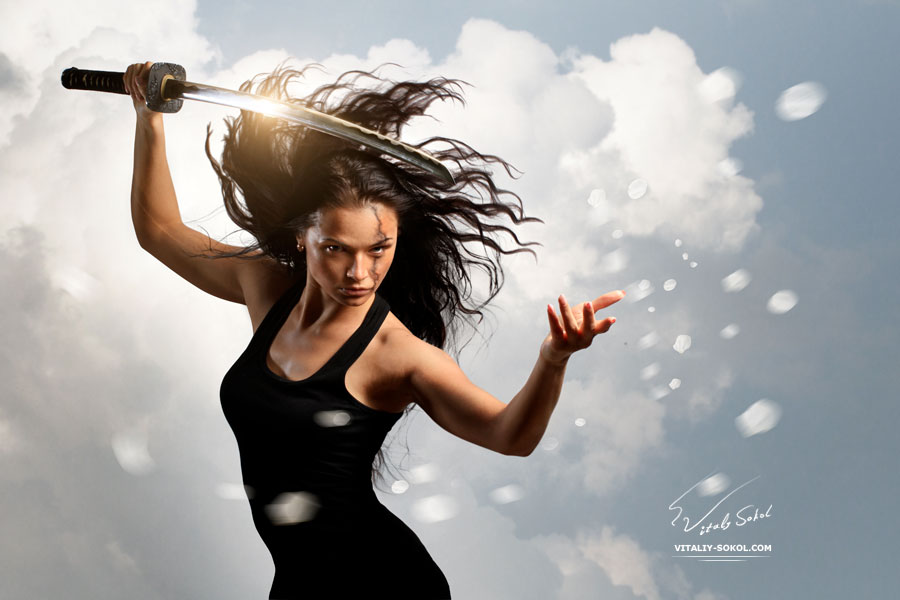 Beautiful aggressive Brunette holding katana sword with cloudy environment