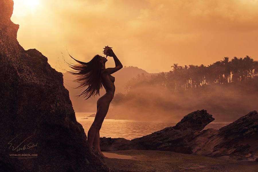 Mermaid playing seashell on sunrise beach