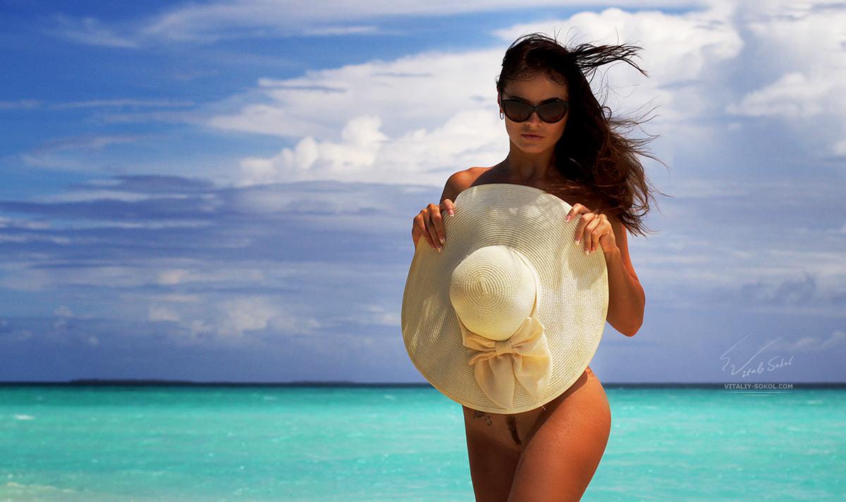 Обнажённая девушка прикрывается шляпкой на мальдивском пляже возле бирюзового моря