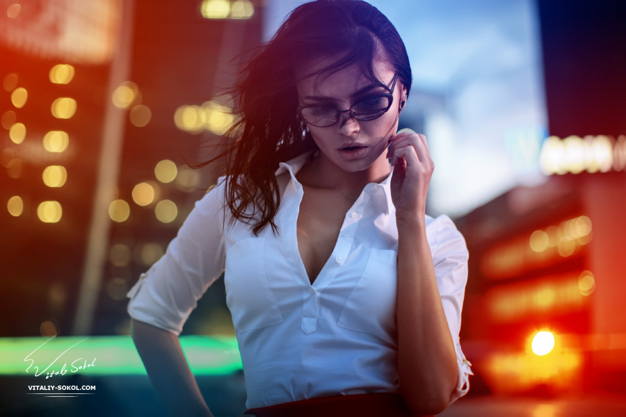 Attractive Brunette wearing glasses in white shirt in front of night city lights. Creative portrait with colorful lights and flares. Привлекательная брюнетка в вечернем городе. Бизнес-леди после после работы.