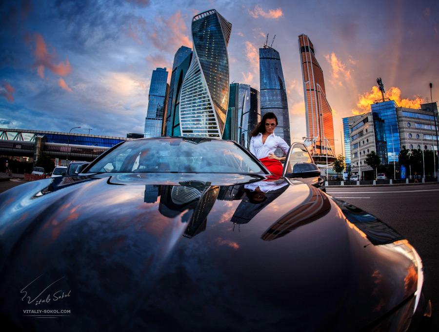 Модель в белой рубашке на фоне вечерних небоскрёбов в закатном освещении открывает дверь автомобиля