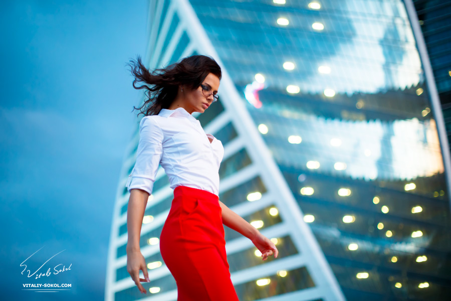 Attractive Business lady in red skirt and white shirt in front of glossy skyscraper with evening lights in windows. Woman wearing glasses walking in business-city with fresh wind in her hair.
