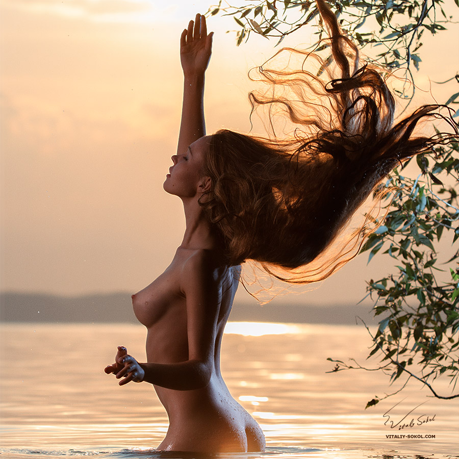 Naked sexy model in a lake water in sunset light