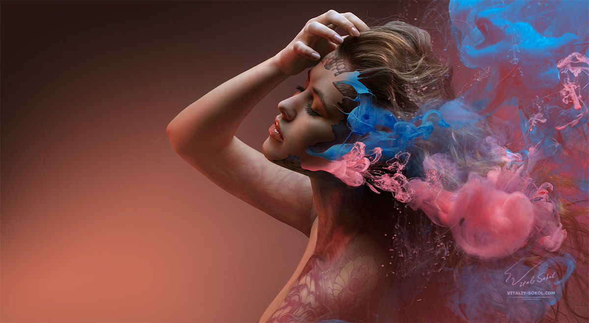 Fantasy fashion model inside colorful clouds. Water paint spreading underwater. Fantastic shapes in deep space. Девушка в окружении облака краски растворённой в воде