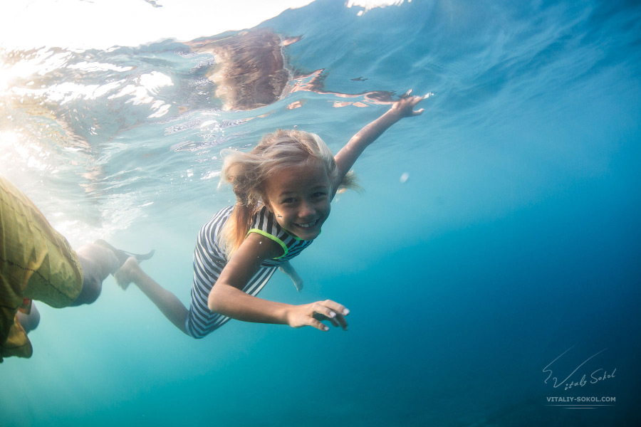 A little girl underwater with sunshine smile. Cute child does not afraid to open eyes in salt water