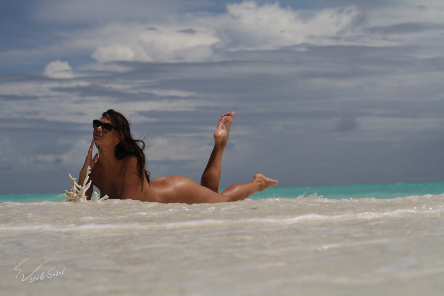 Naked model tanning and posing on maldivian water at sandy beach