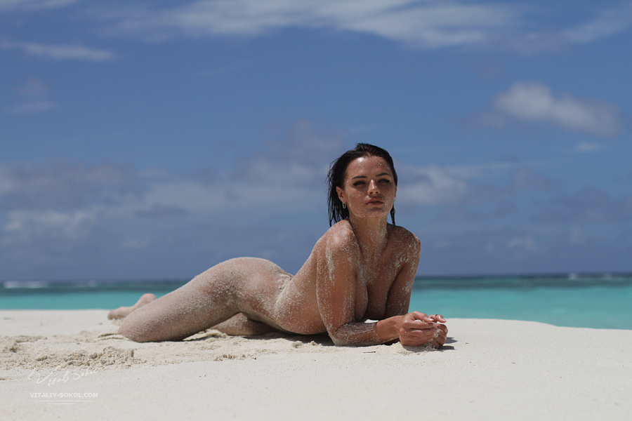 Naked model posing on maldivian sandy beach