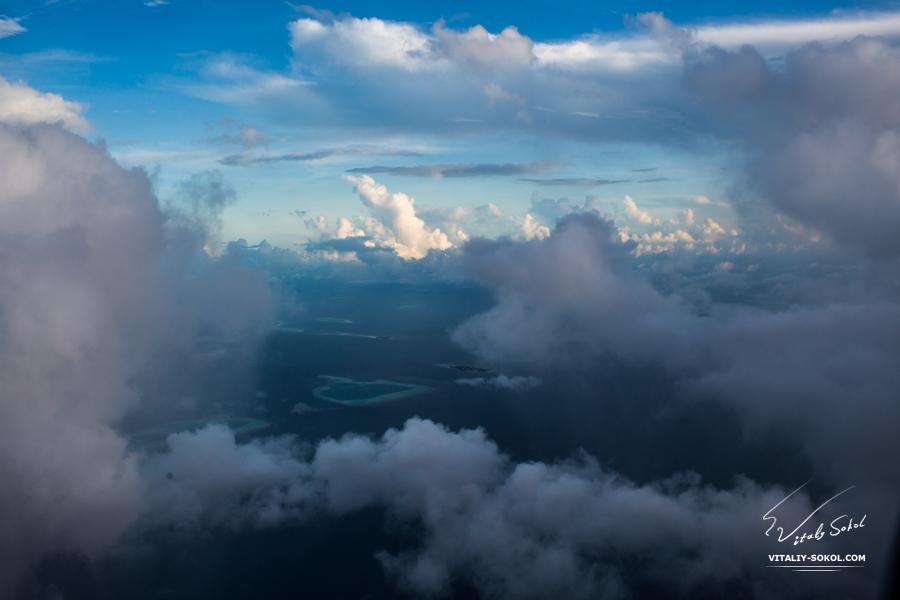 Мальдивы, утренний рейс, вид из иллюминатора самолёта. Облака и острова
