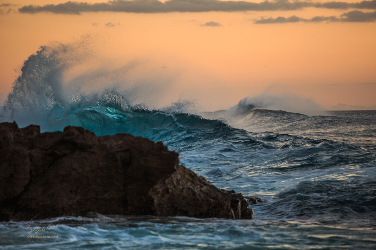 Stock Photo:Beautiful tropical sunset surfing wave crashing on dark rock in the ocean. An orange sky right after sunset. Vibrant blue color of breaking splashes at evening time.