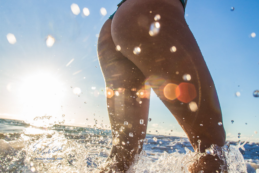 Beautiful female ass in splashes near ocean with sunlight