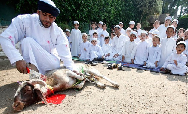 Мастер показывает детям, как закалывать жертву