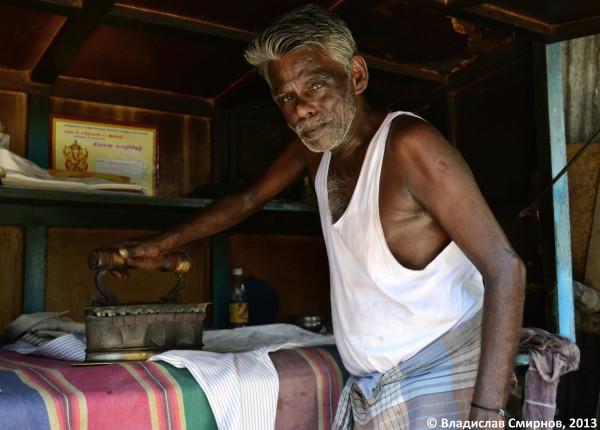 Мужчина гладящий белье старым утюгом на углях в Ченнае
