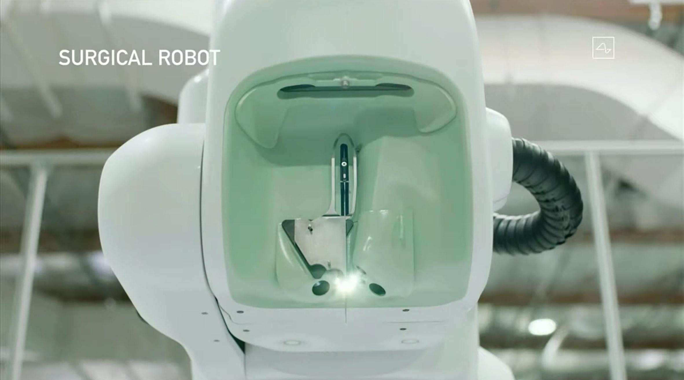 """Спроектированная """"с нулевым пространством для ошибок"""", головка машины удерживает и направляет иглу, которая выполняет операцию, и содержит большое количество камер и датчиков для захвата всего мозга.Асимметричный кузов имеет """"автомобильную кривизну"""" и обеспечивает механику управляемого движения. Эта часть робота, которая движется по пяти осям, была спроектирована так, чтобы движение казалось """"чистым и легким"""".Корпус крепится к основанию, которое обеспечивает взвешенную опору для всей конструкции и удерживает вычислительную мощность для работы всей машины."""