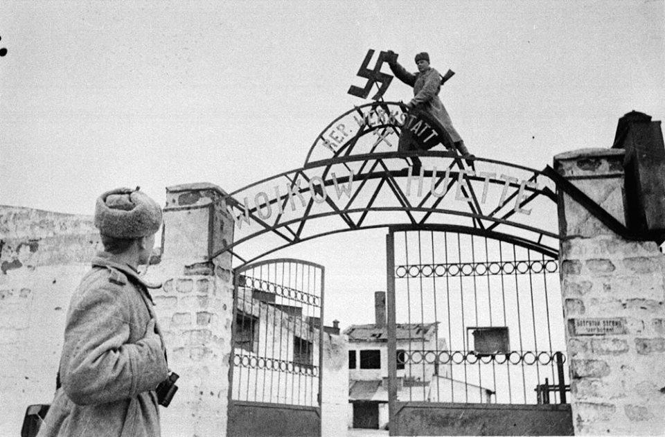 На фото советский солдат срывает нацистскую свастику с ворот металлургического завода им. Войкова в освобождённой Керчи