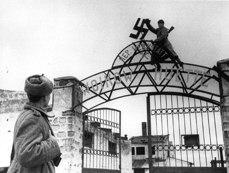 Советские бойцы сбивают фашистскую свастику с входа на территорию завода им. Войкова в освобожденном городе Керчи