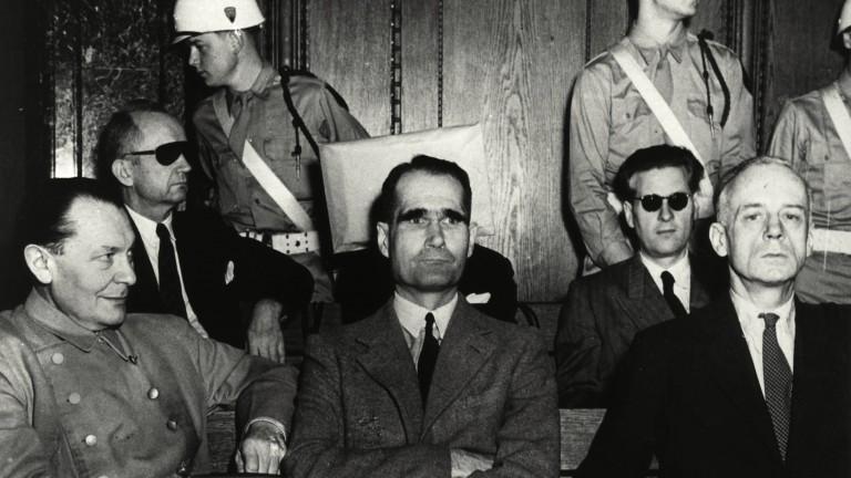 В первом ряду слева направо: Герман Геринг (признан виновным по всем четырем пунктам обвинения), Рудольф Гесс (виновен по первому и второму обвинениям, не виновен по третьему и четвертому обвинениям) и Иоахим фон Риббентроп (виновен. по всем четырем обвинениям). В заднем ряду слева направо Карл Дёниц (невиновен по первому обвинению, виновен по второму и третьему обвинениям, не обвиняется в четвертом преступлении), Эрих Рэдер (скрыт; виновен по первому, второму и третьему пунктам). обвинения, не обвиняемый в четвертом преступлении), и Бальдур фон Ширах (невиновен по первому обвинению, виновен по четвертому обвинению, не обвиняется во втором и третьем преступлениях). Из-за яркого света камер, снимавших процесс, обвиняемым были предоставлены темные очки. Фотограф неизвестен.