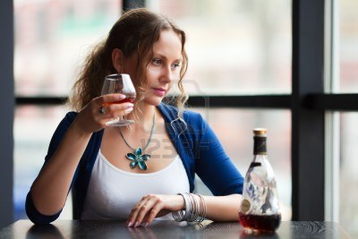 7011459-beautiful-young-woman-drinking-cognac-at-a-restaurant