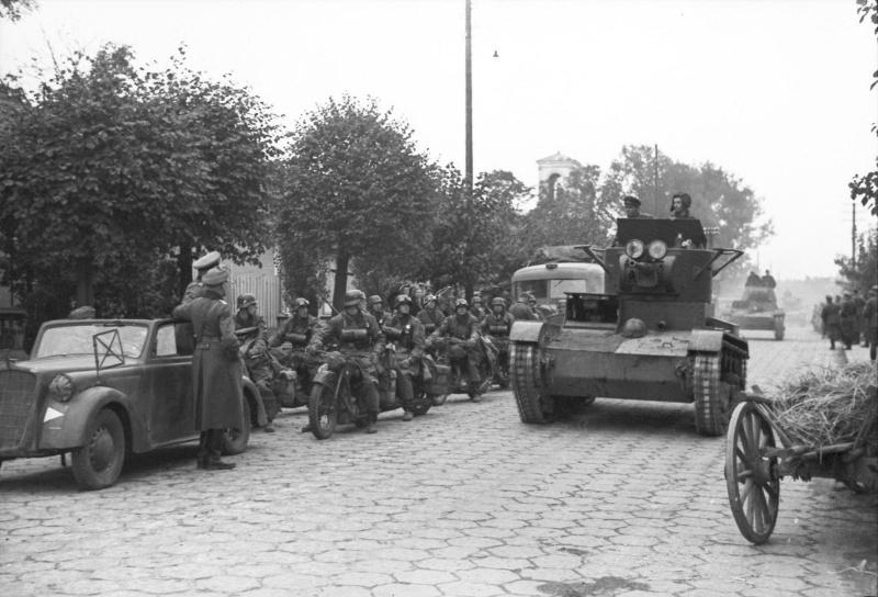 Танки Т-26 из состава 29-й танковой бригады Красной Армии входят в Брест-Литовск. Слева — подразделение немецких мотоциклистов и офицеры вермахта у автомобиля Opel Olympia