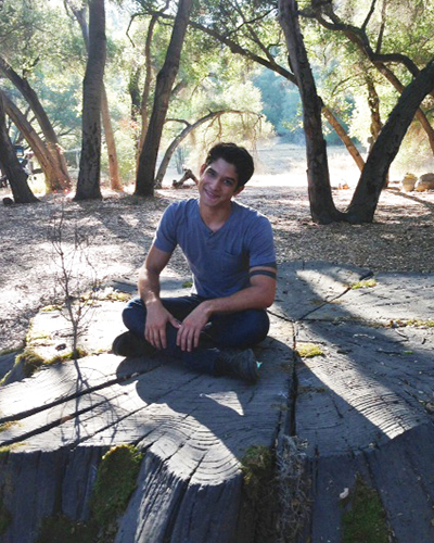 fig 1. human puppy tyler posey sits on stump