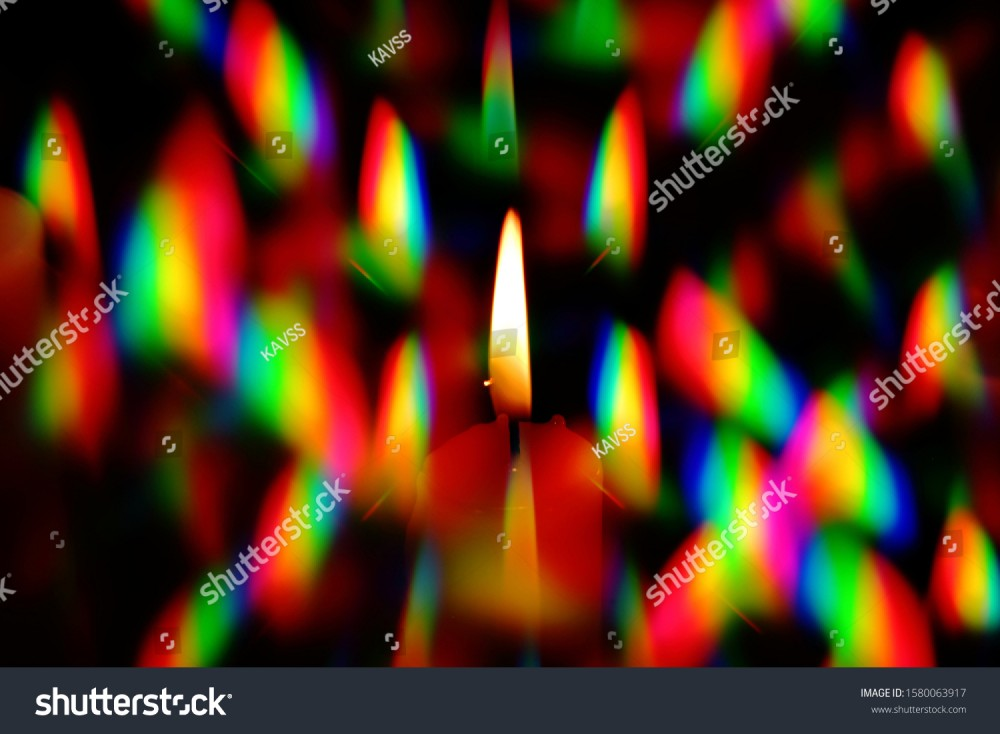 stock-photo-flame-of-a-candle-surrounded-by-a-halo-of-multi-colored-glares-was-photographed-through-two-1580063917.jpg