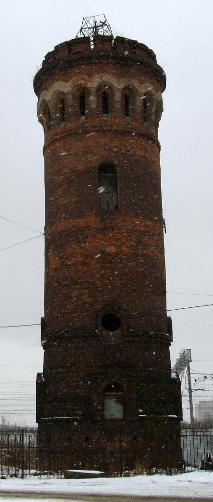 Самая первая водонапорная башня по Вологодской ЖД, ежели считать от Обухова. И кстати, довольно оригинальная. Жаль только, окружающий пейзаж не очень...