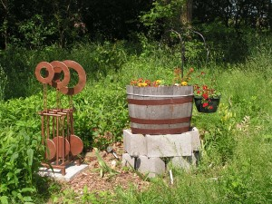 The yard sculpture is now standing beside the barrel garden.