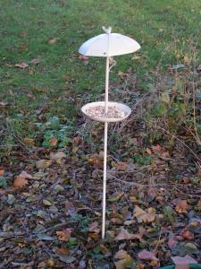 The metal birdfeeder is in the forest garden near the hopper feeder.